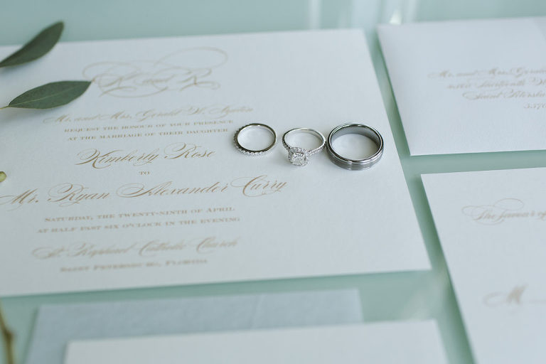 Engagement Ring and Wedding Bands on Elegant Gold Script on White Wedding Invitation Suite