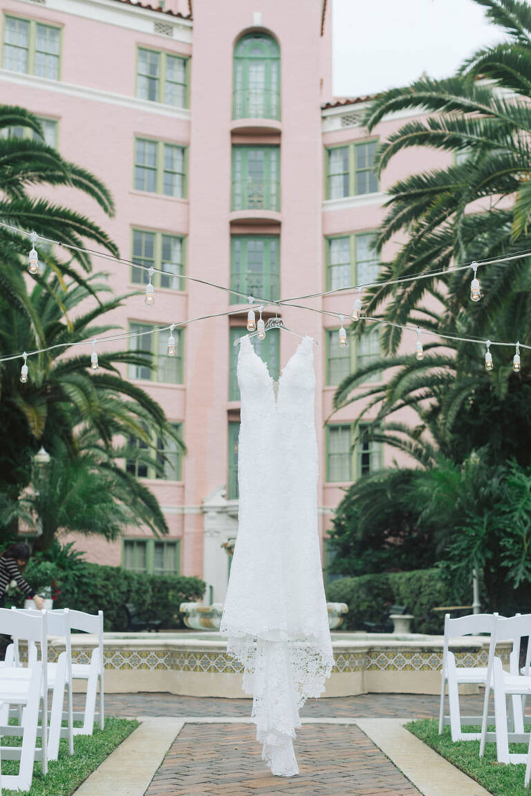 Luxurious Lace Wedding Dress Hanging in Tea Garden at Historic Renaissance Vinoy Hotel, Outdoor Wedding Ceremony in Tropical Courtyard | Tampa Bay Wedding Planner Parties A La Carte