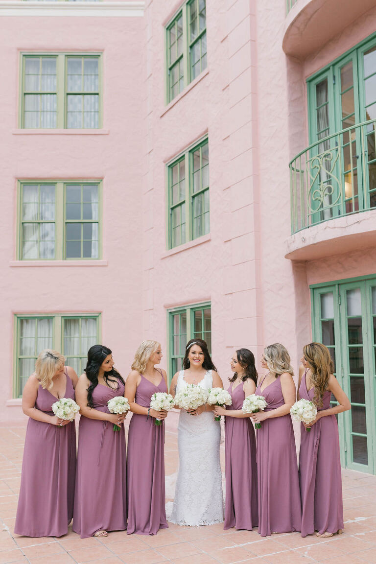 Classic Florida Bride Wearing Romantic Lace Wedding Dress Holding White and Blush Pink Rose Bridal Bouquet, Bridesmaids in Long Purple Wedding Dresses In Courtyard of Vinoy Renaissance Hotel | St. Petersburg Wedding and Event Planner Parties A La Carte